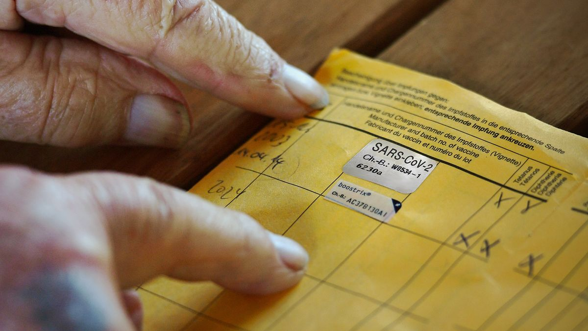 Impfausweis mit Eintrag für die Corona-Schutzimpfung, Hände eines älteren Mannes (Symbolbild).