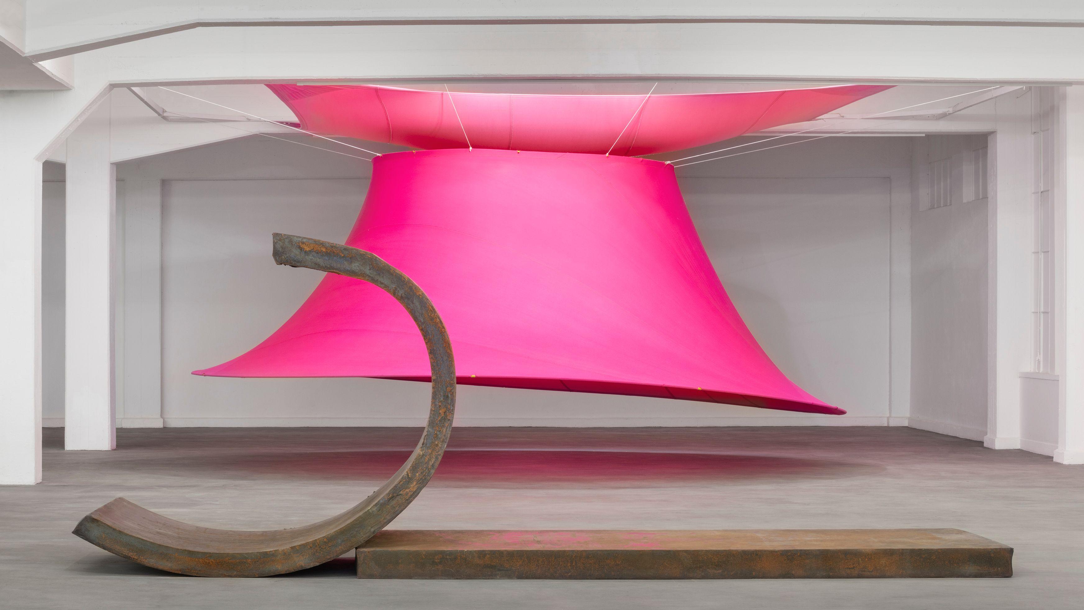 Foto eines Ausstellungsraums, in dem ein großes glockenartiges, nach unten offenes leuchtend pinkes Zelt hinter einer schweren, aber elegant geformten Stahlskulptur hängt.
