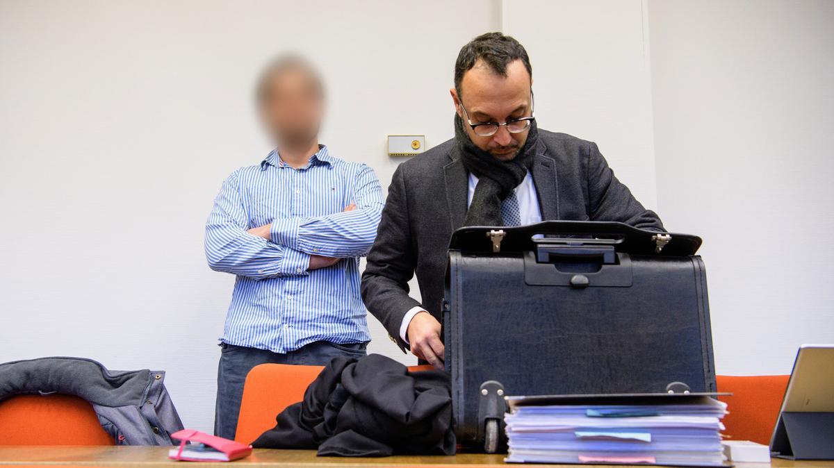 Im Bild ist Verteidiger Adam Ahmed. Hinter ihm steht der Angeklagte Nidal A.