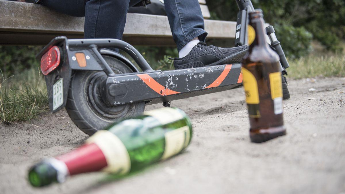 Vor einem E-Scooter liegen und stehen leere Flaschen alkoholischer Getränke.