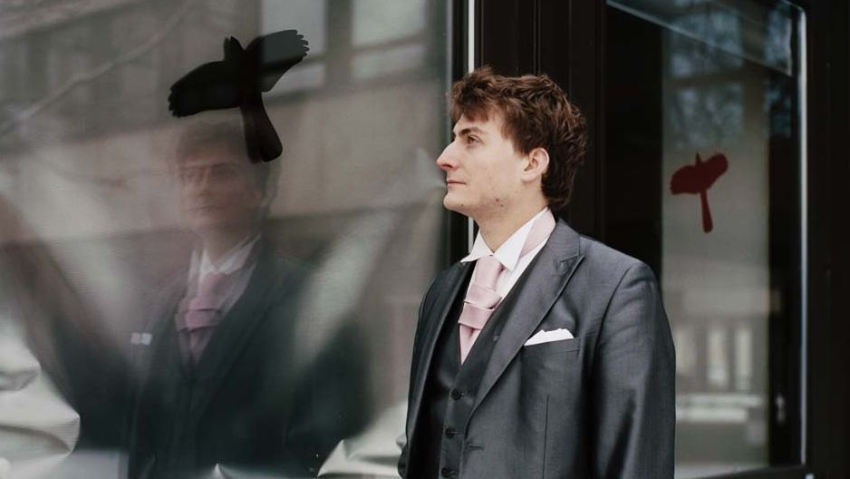 Fensterscheibe mit Vogel und davor ein nachdenklicher Mann mit Anzug: Sebastian Krämer