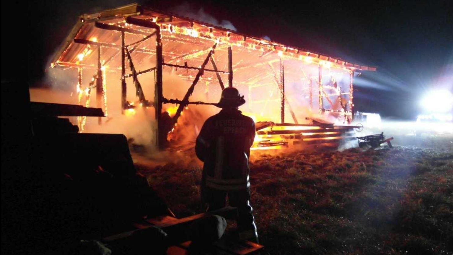 Ein Mitglied der Freiwilligen Feuerwehr Denklingen steht vor der brennenden Scheune.