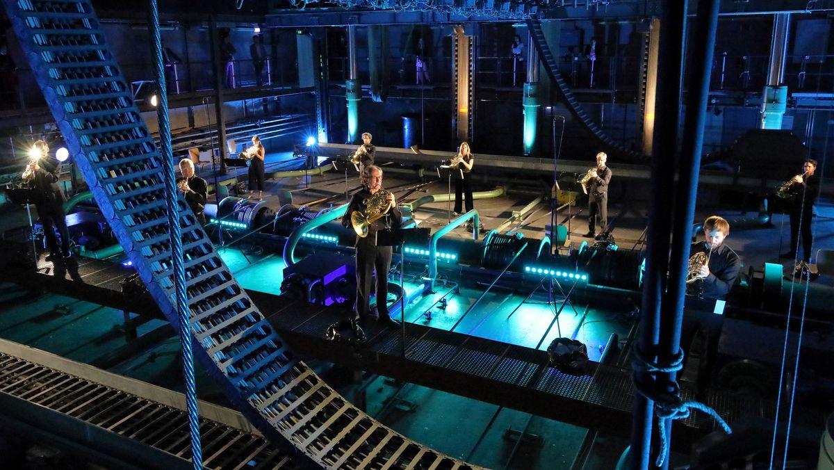 Blick auf die improvisierte Bühne: Mehrere Hornisten spielen im Stehen und mit Abstand