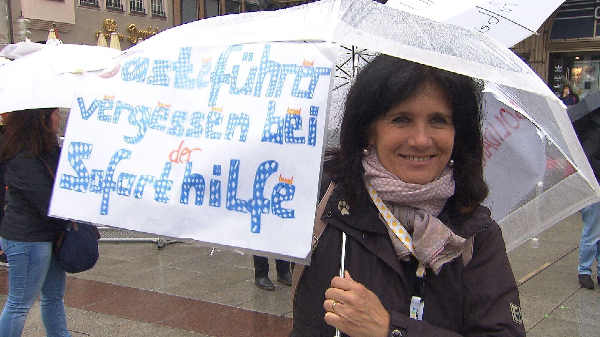 """Eine Frau steht im Regen, am Schirm ein Plakat mit der Aufschrift """"Gästeführer vergessen bei der Soforthilfe"""""""