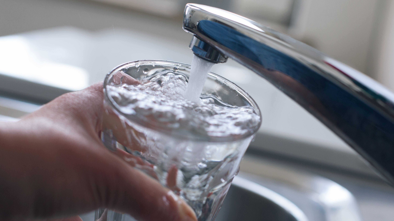 Ein Glas wird mit Wasser aus dem Wasserhahn gefüllt