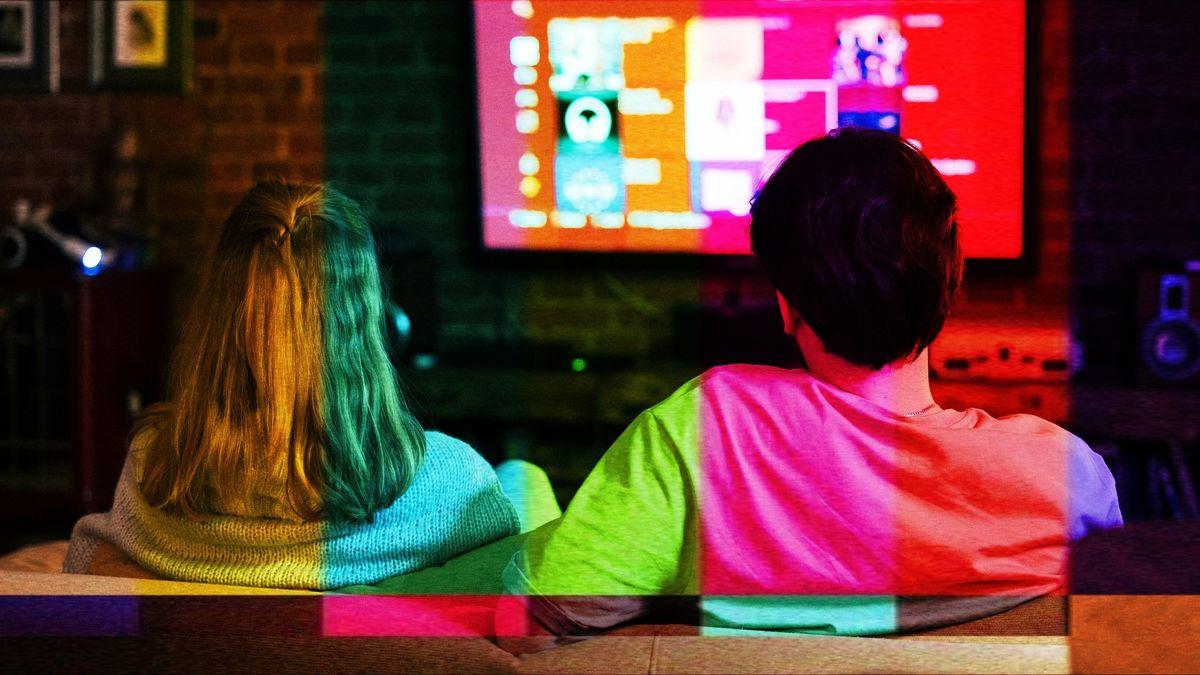 Junges Paar auf dem Sofa vorm Fernseher, von hinten gesehen