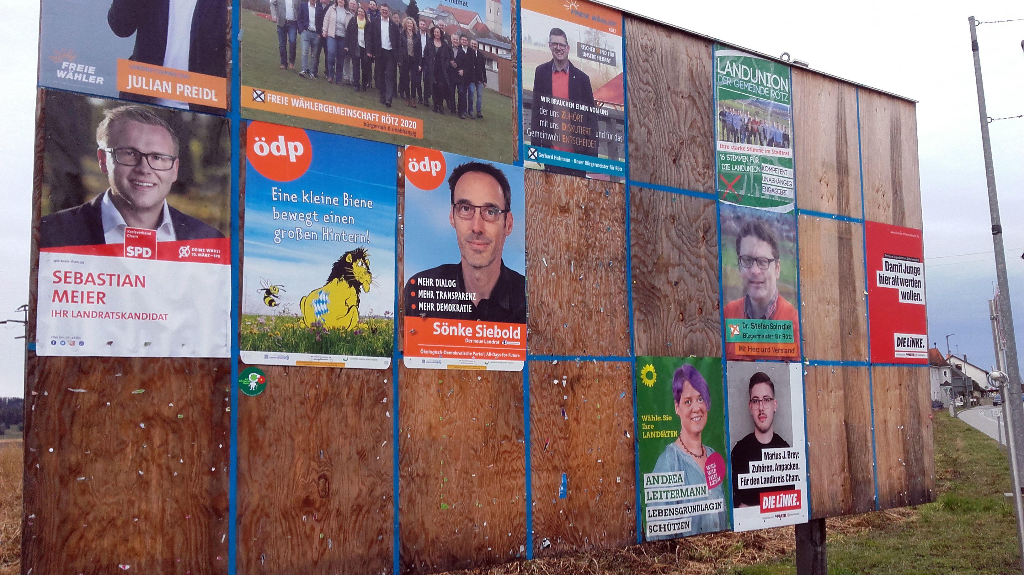 Eine öffentliche Plakatwand mit Wahlplakaten.