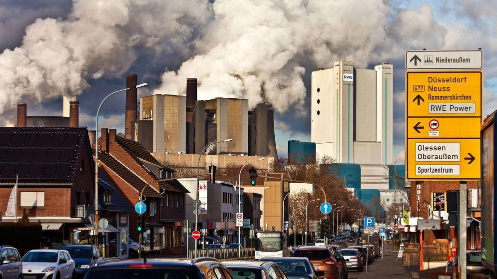 Eine Straße in Niederaußem mit Braunkohlekraftwerk im Hintergrund.