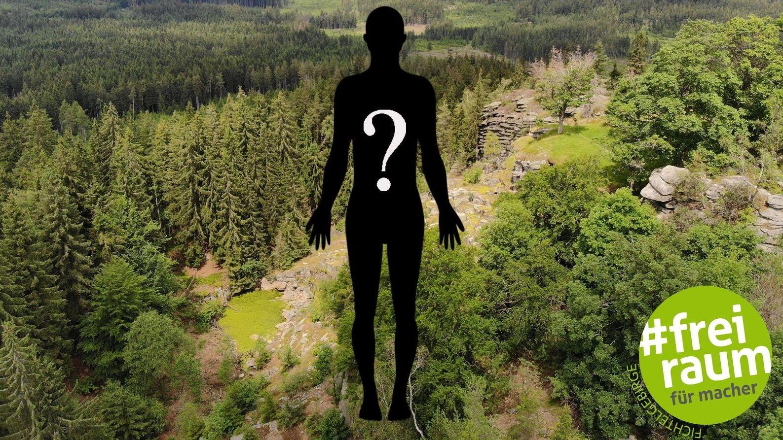 Eine schwarze Figur mit einem weißen Fragezeichen auf dem Rücken schwebt über dem Fichtelgebirge mit vielen grünen Bäumen.