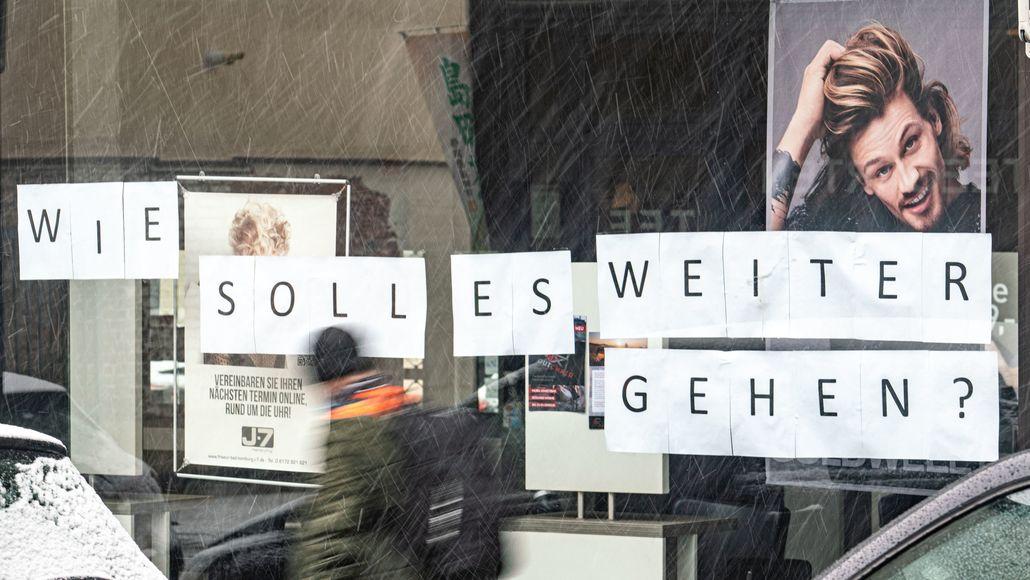 """Auf der Scheibe eines Friseurgeschäfts steht der in DinA4-Lettern der Schriftzug: """"Wie soll es weitergehen?"""""""