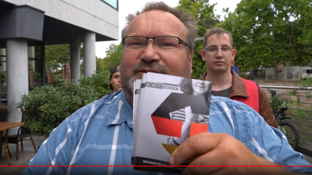 """Ein korpulenter Mann hält Flyer in die Kamera, auf denen ist ein Logo in schwarz-rot-gold zu sehen. Das Wort """"Schutzzone"""" ist lesbar."""