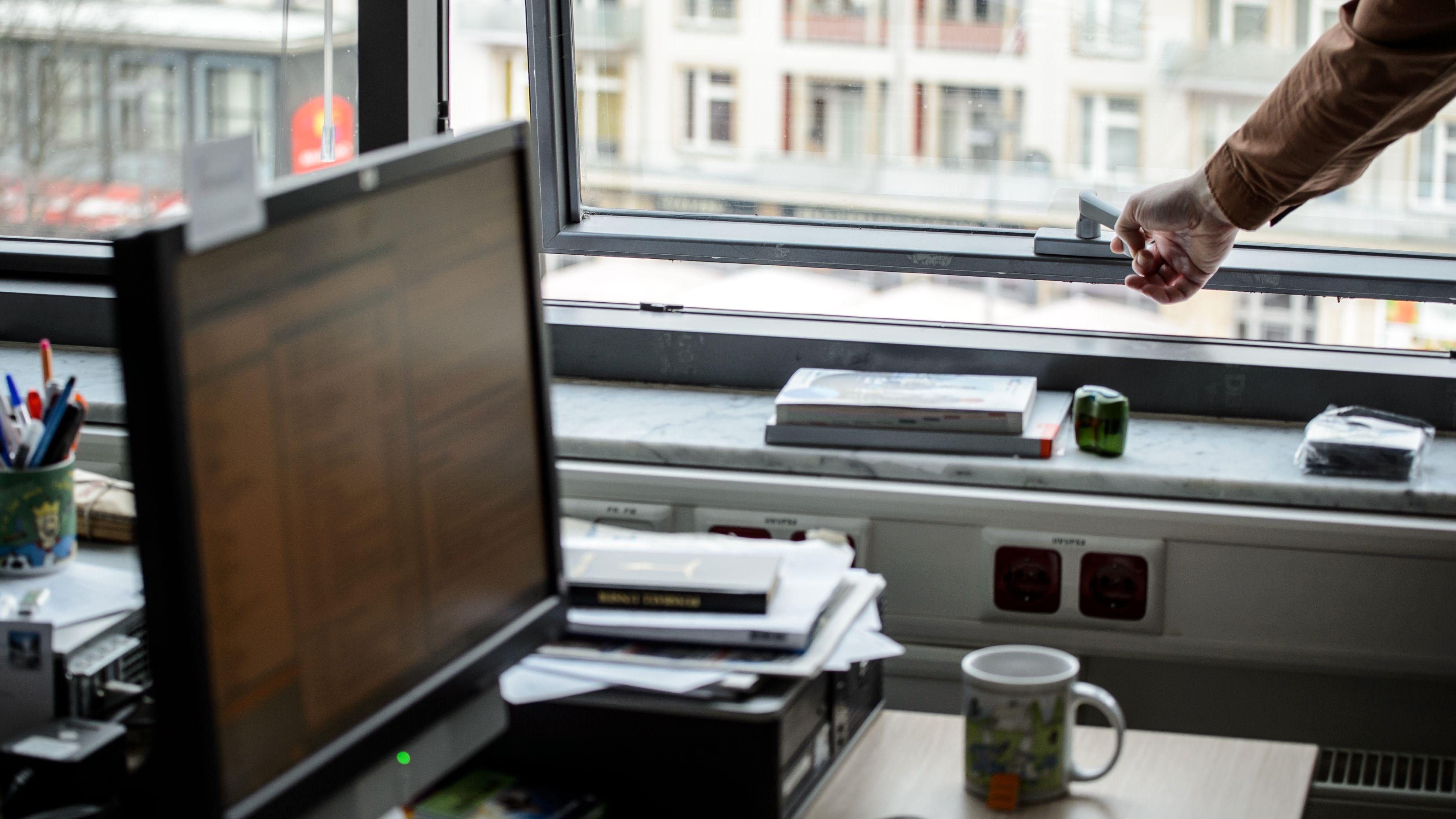 Ein Angestellter steht in einem Büro an seinem Schreibtisch und öffnet das Fenster