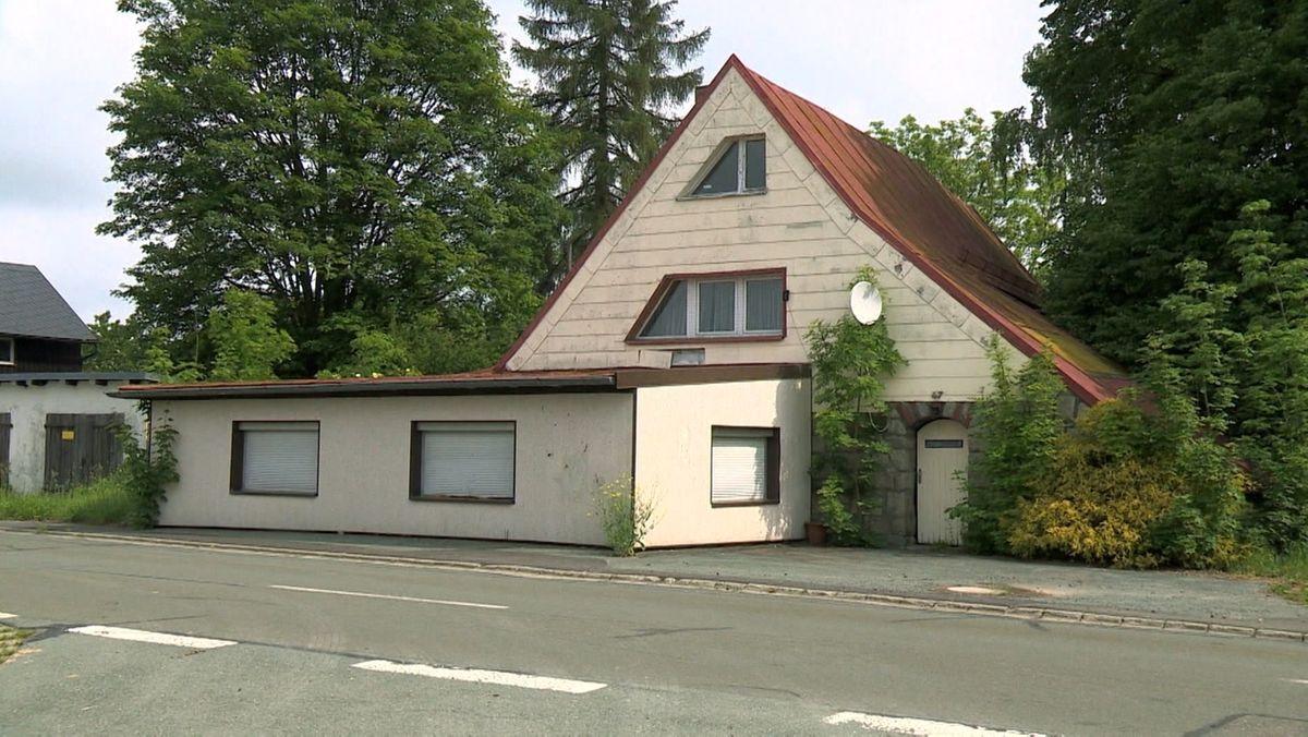 Ein Haus mit rotem Dach, davor ein flacher Anbau, dahinter hohe Laubbäume.