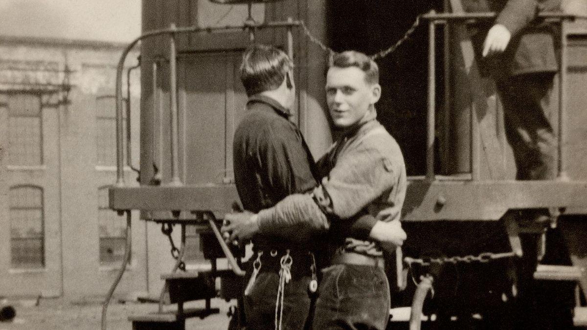 Männerpaar steht auf den  Schienen