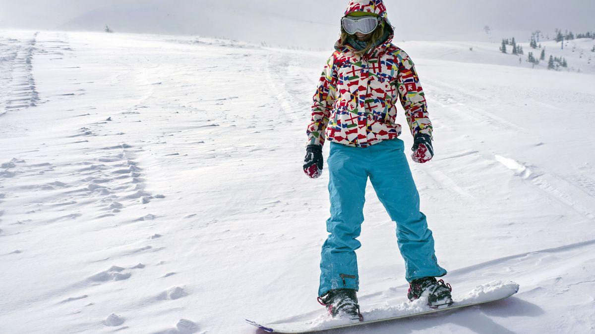 Verhüllter Snowboarder auf einer Piste (Symbolbild)