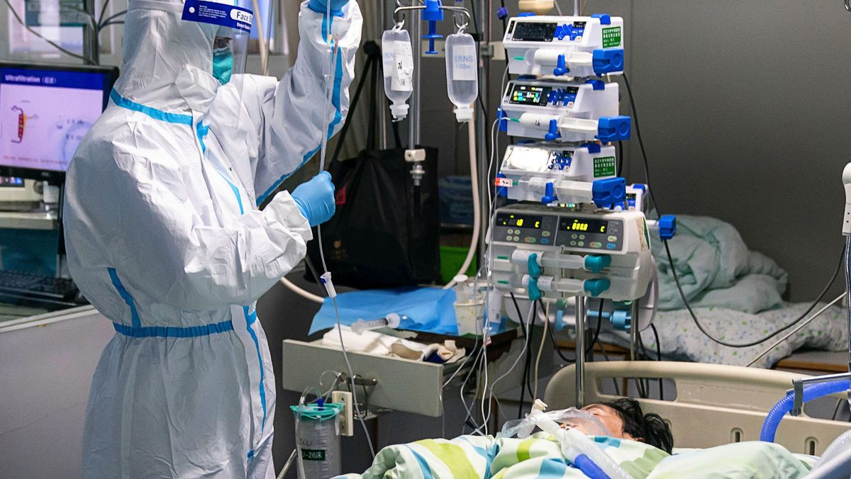 """Ein medizinischer Mitarbeiter überprüft den Tropf eines Patienten auf der Intensivstation des Krankenhauses """"Zhongnan"""" der Universität Wuhan."""
