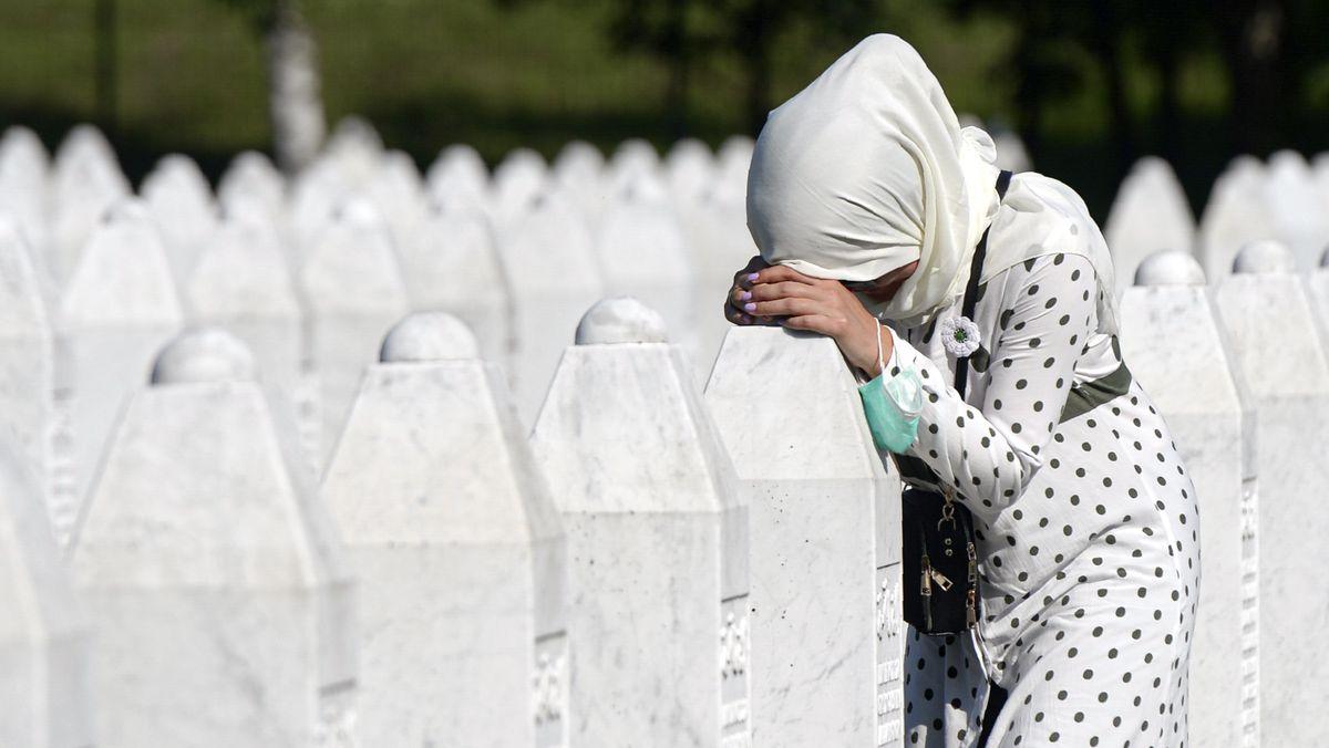 Eine Frau trauert auf dem Friedhof der Gedenkstätte Potocari in der Nähe von Srebrenica an einem Grab.