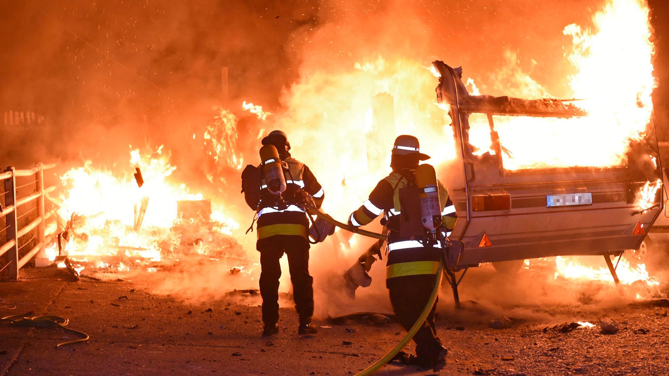 Zwei Feuerwehrkräfte löschen zwei brennende Wohnwagen in der Münchner Isarvorstadt