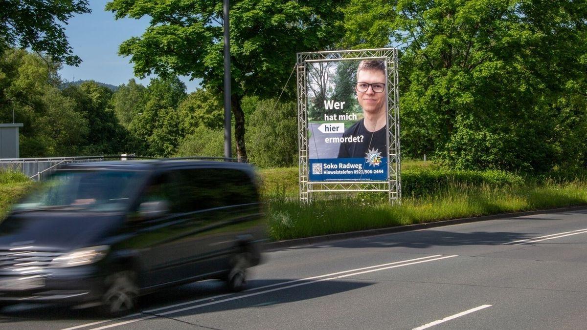 """Ein Plakat der Polizei steht an einer Straße und zeigt das Bild eines getöteten Radfahrers, dazu der Satz """"Wer hat mich hier ermordet?"""""""