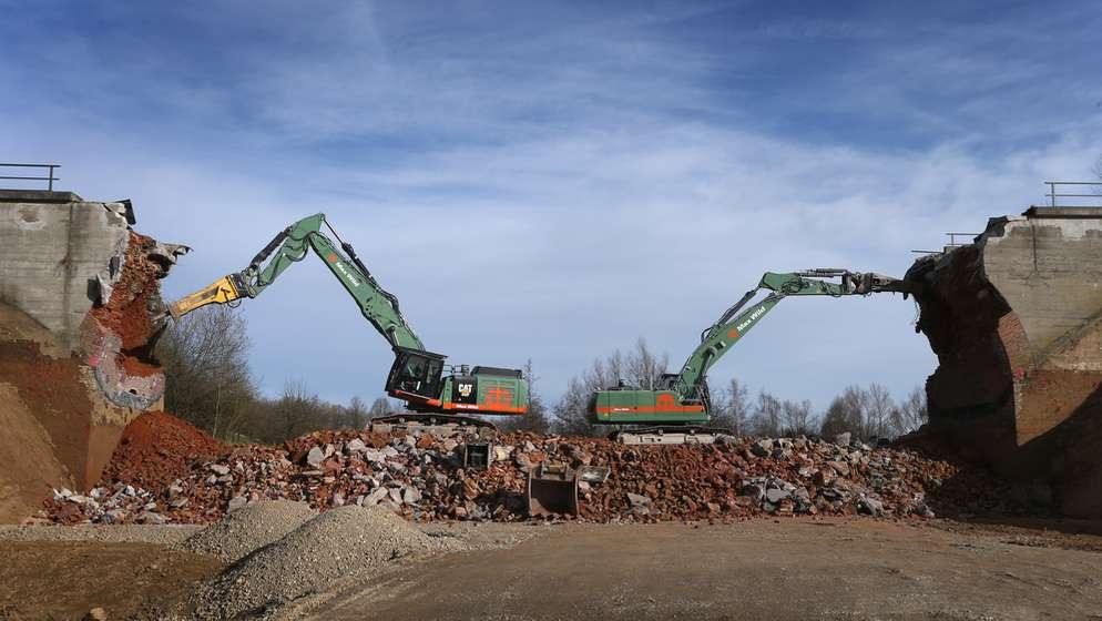 Bauarbeiten zur Modernisierung der Bahngleise im Allgäu: Zwei Bagger reisen ein Viadukt ein. | Bild:dpa