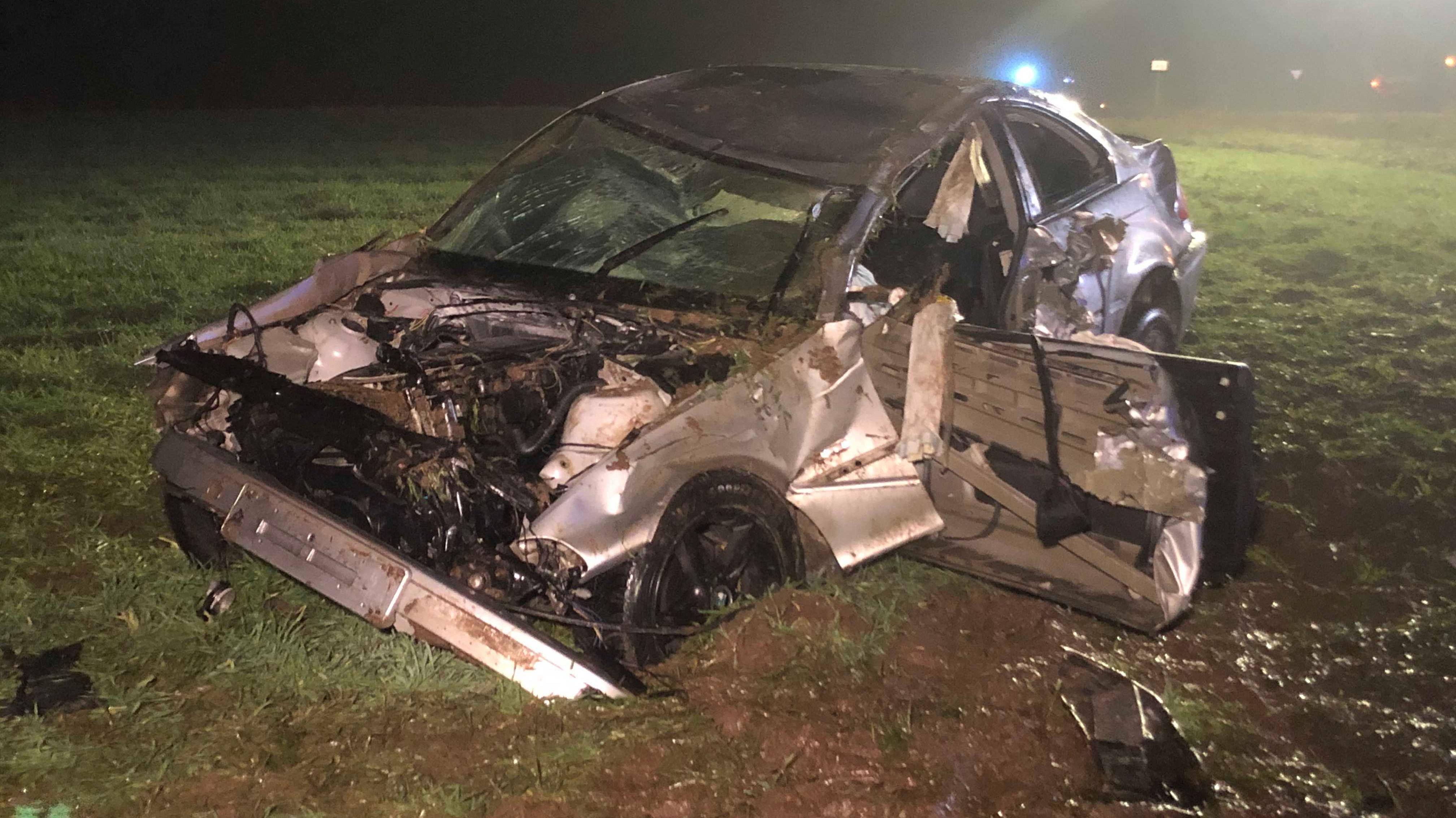Ein schwer beschädigtes Auto steht auf einer Wiese