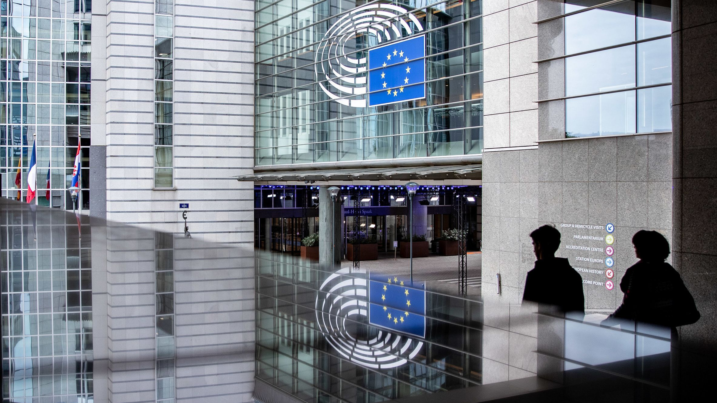 Ein Eingang zum Europäischen Parlament in Brüssel spiegelt sich in einer Glasfläche.