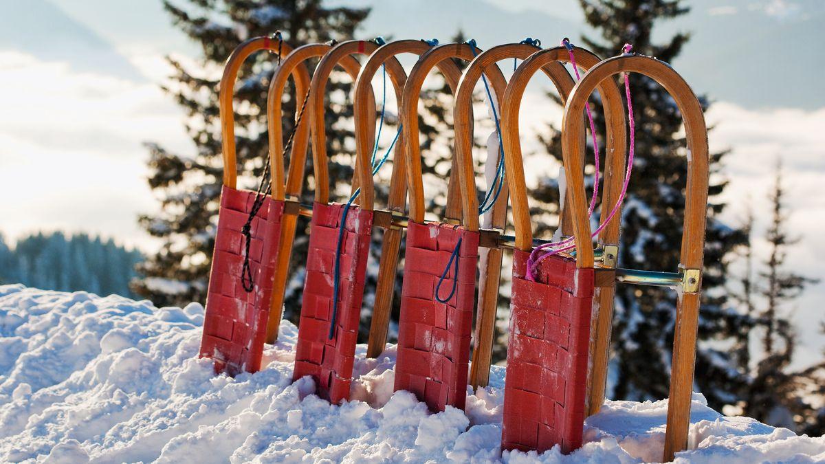 Vier Holzschlitten stehen im Schnee