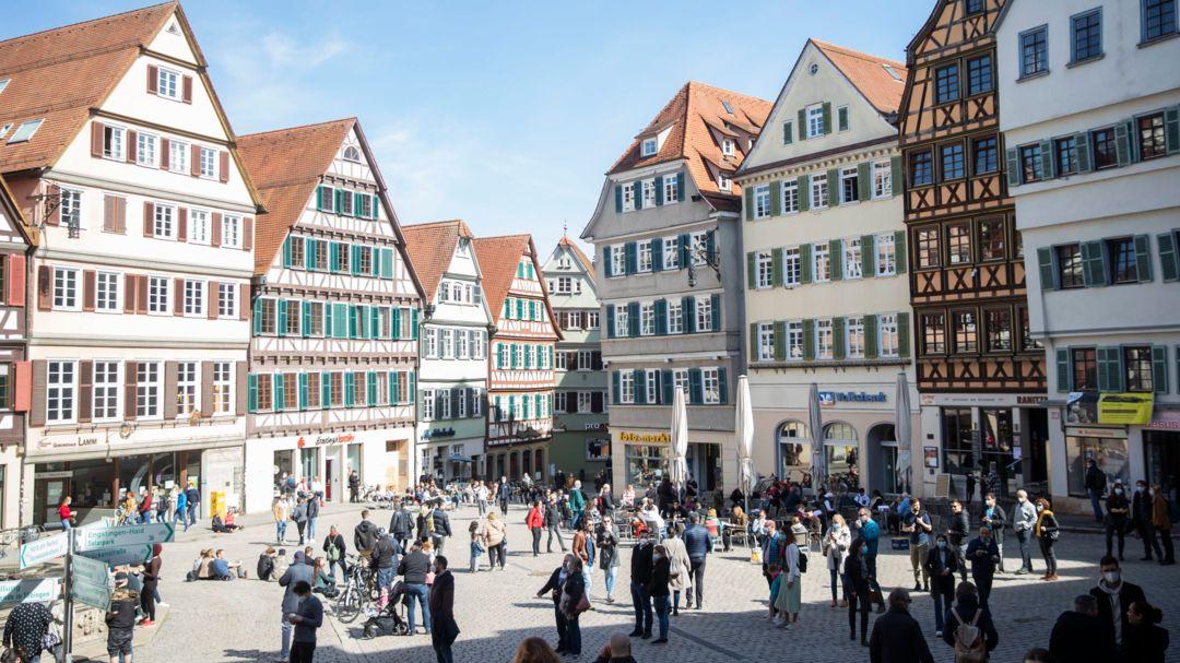 Menschen sitzen auf dem Tübinger Rathausplatz in Cafes.
