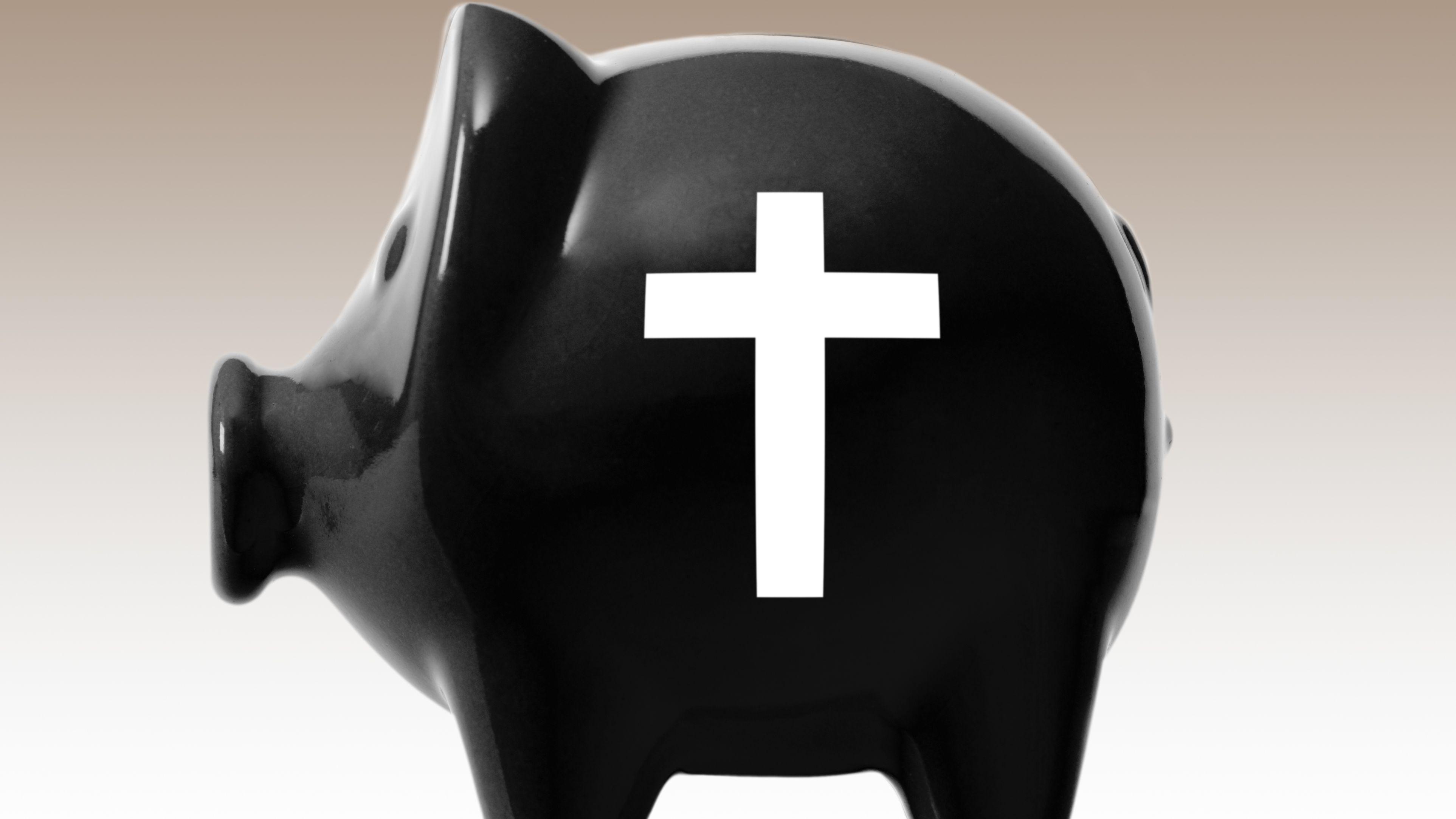 schwarzes Sparschwein mit weißem Kreuz