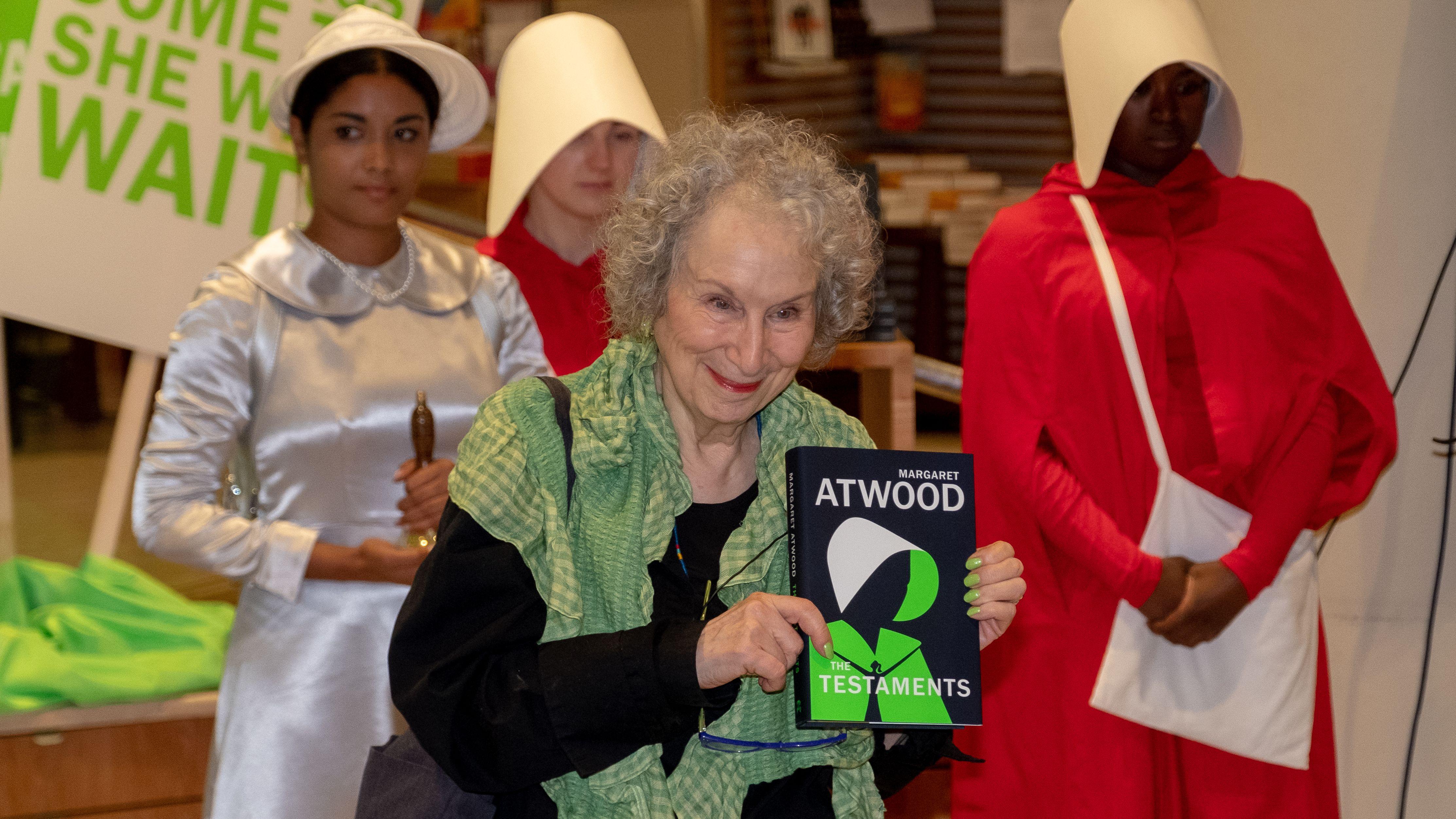 Margaret Atwood hält nach der Lesung in London ihren neuen Roman in die Kameras, im Hintergrund verkörpern drei Frauen in Schwesternkostümen ihre drei Romanheldinnen