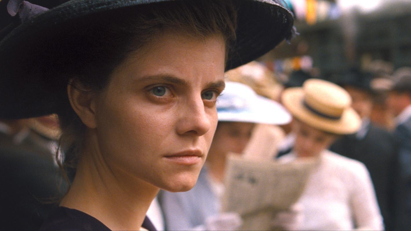 """Eine junge Frau mit Hut blickt über die Schulter (Filmszene aus """"Sunset"""" von László Nemes)."""