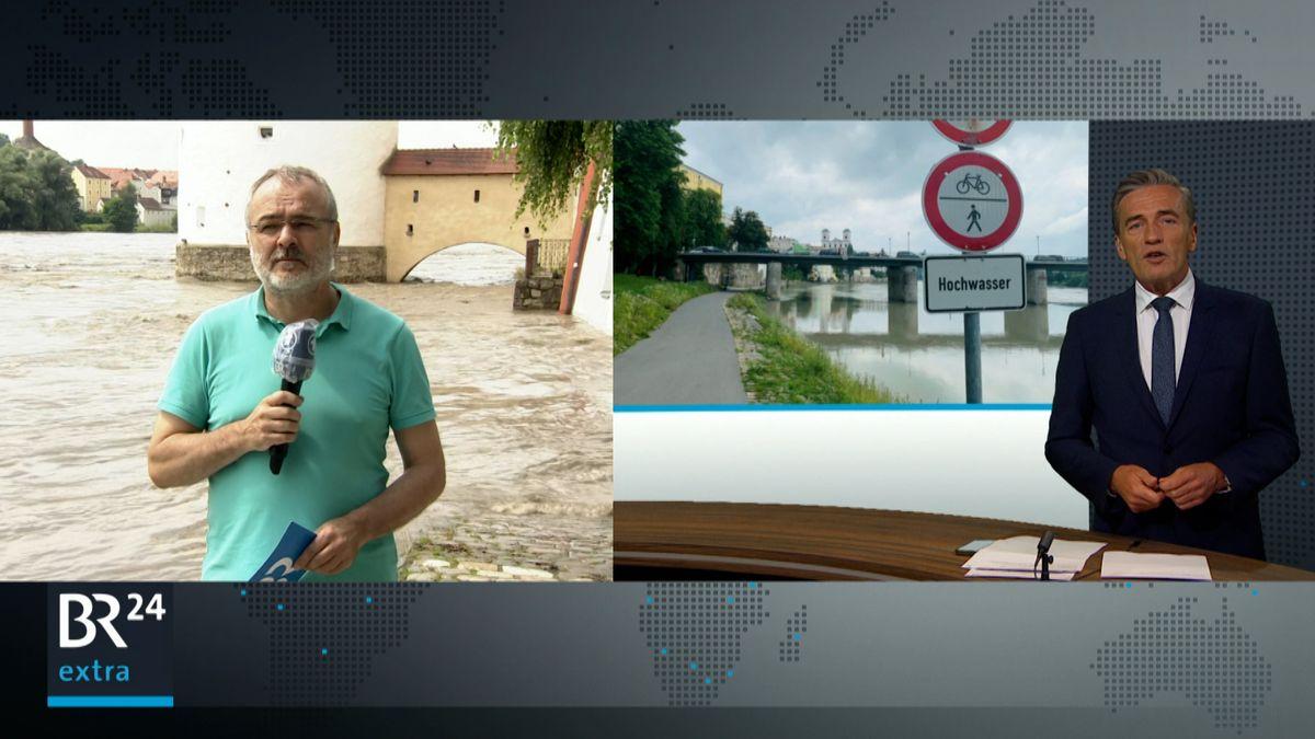 Moderator Stefan Scheider aus dem BR-Studio in München (rechts im Bild) fragt Reporter Martin Gruber (links im Bild), der in Passau am über die Ufer getretenen Inn steht in einer live-Sendung nach der aktuellen Hochwasser-Situation