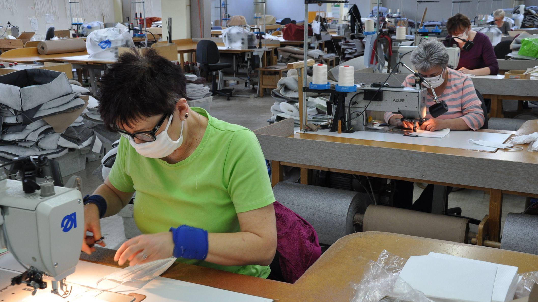 Frauen sitzen an Nähmaschinen und fertigen Atemschutzmasken her.