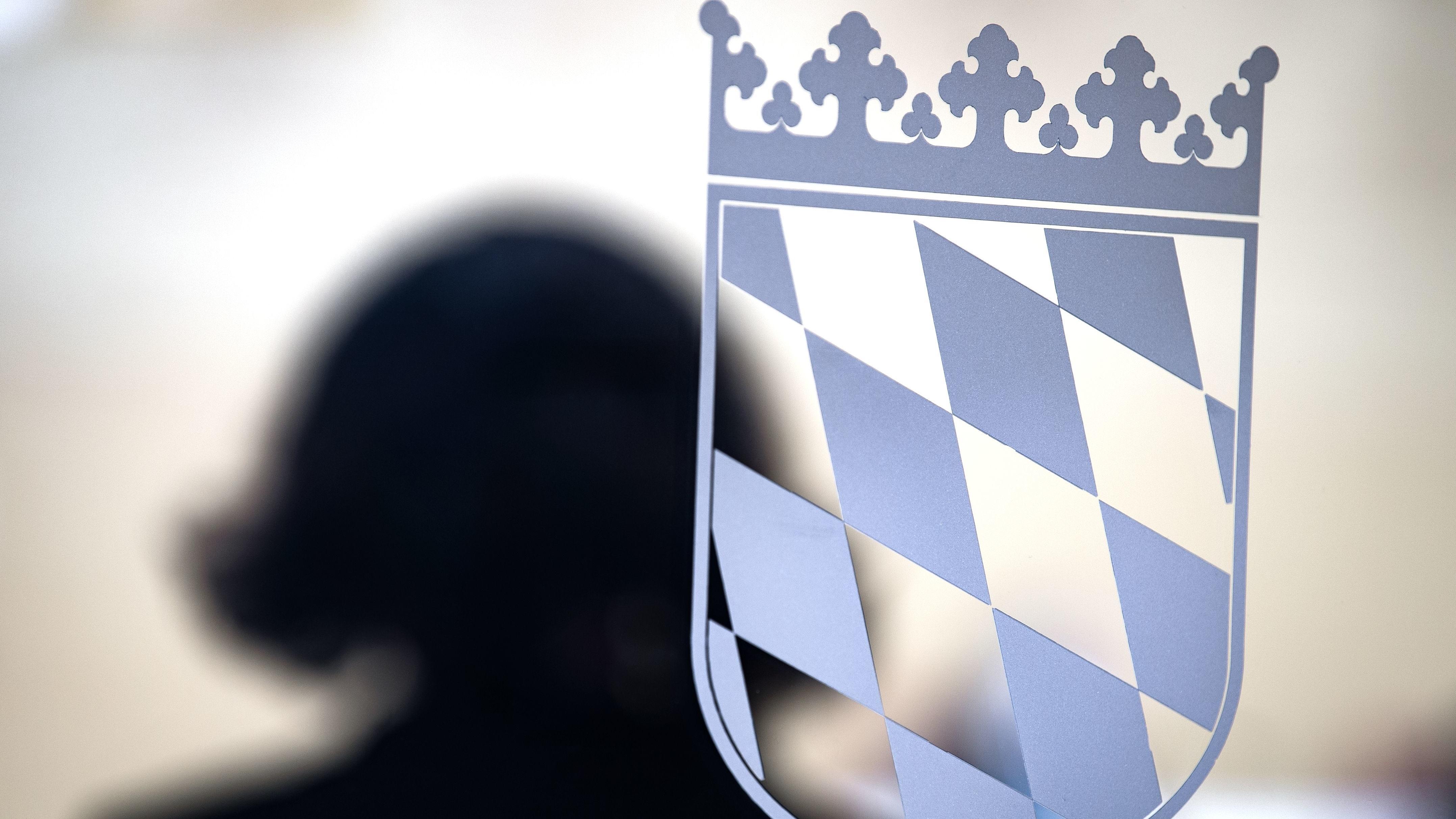 Schatten einer Frau neben dem Wappen der Bayernraute