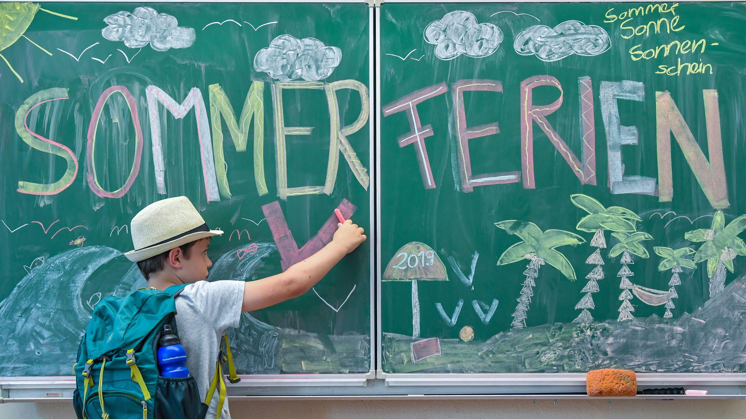 Ein Schüler malt mit Kreide ein Sommerferienbild an die Tafel