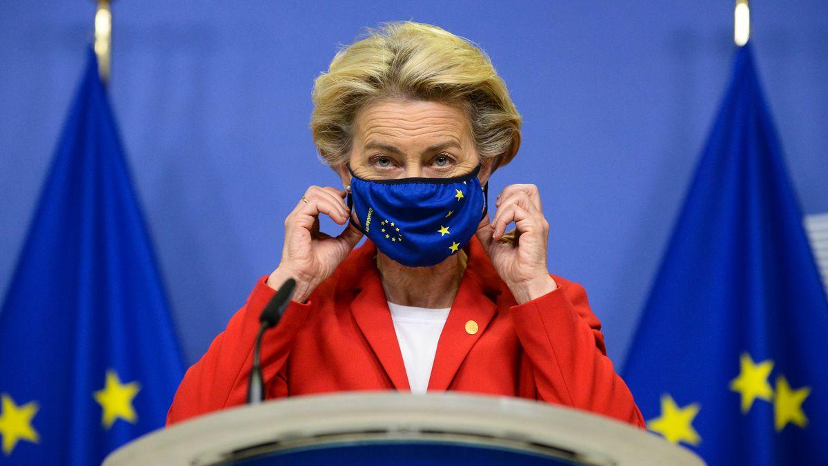 Ursula von der Leyen steht mit einer blauen EU-Maske vor einer EU-Flagge