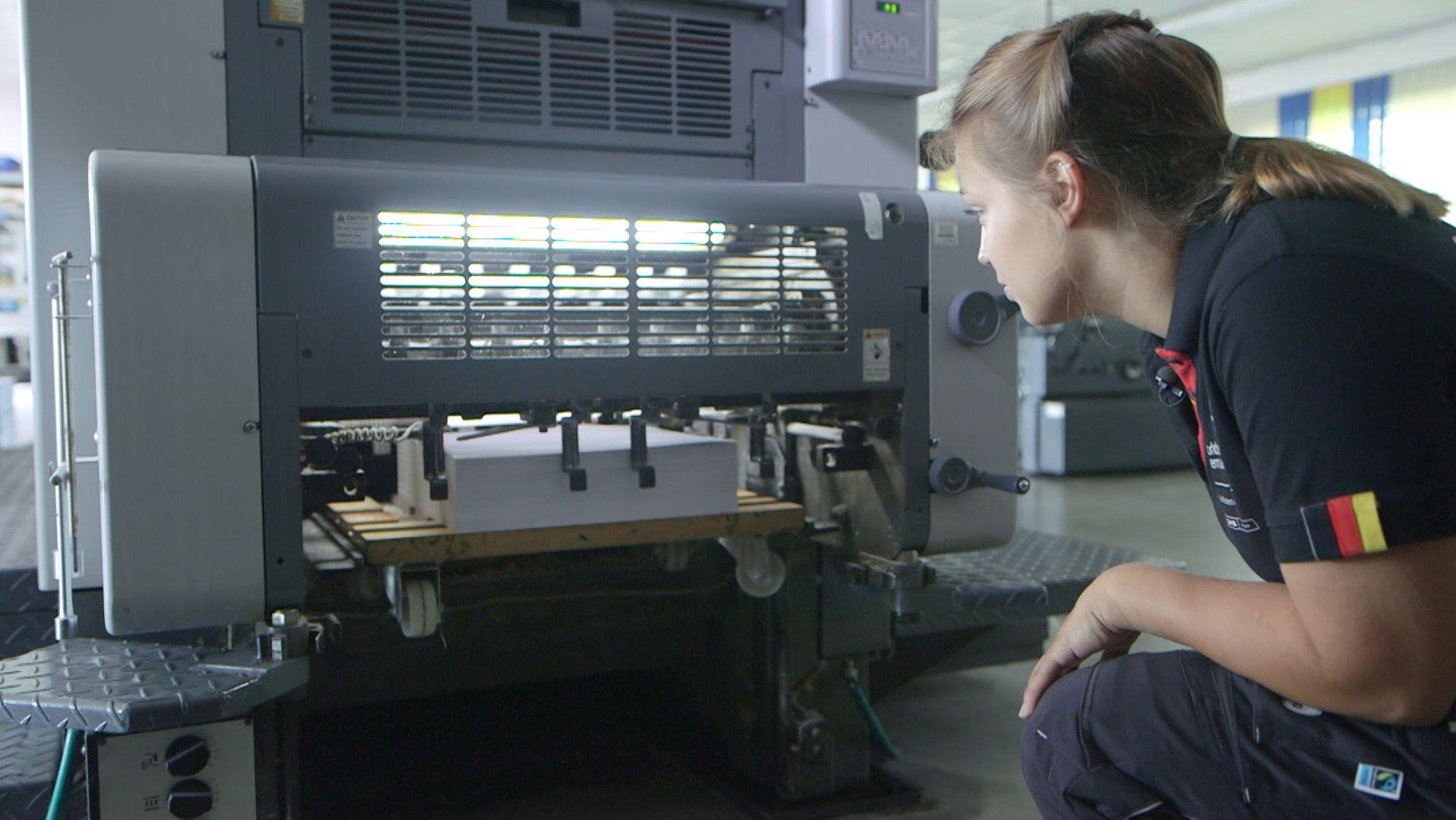 Junge Frau vor Drucktechnikmaschine