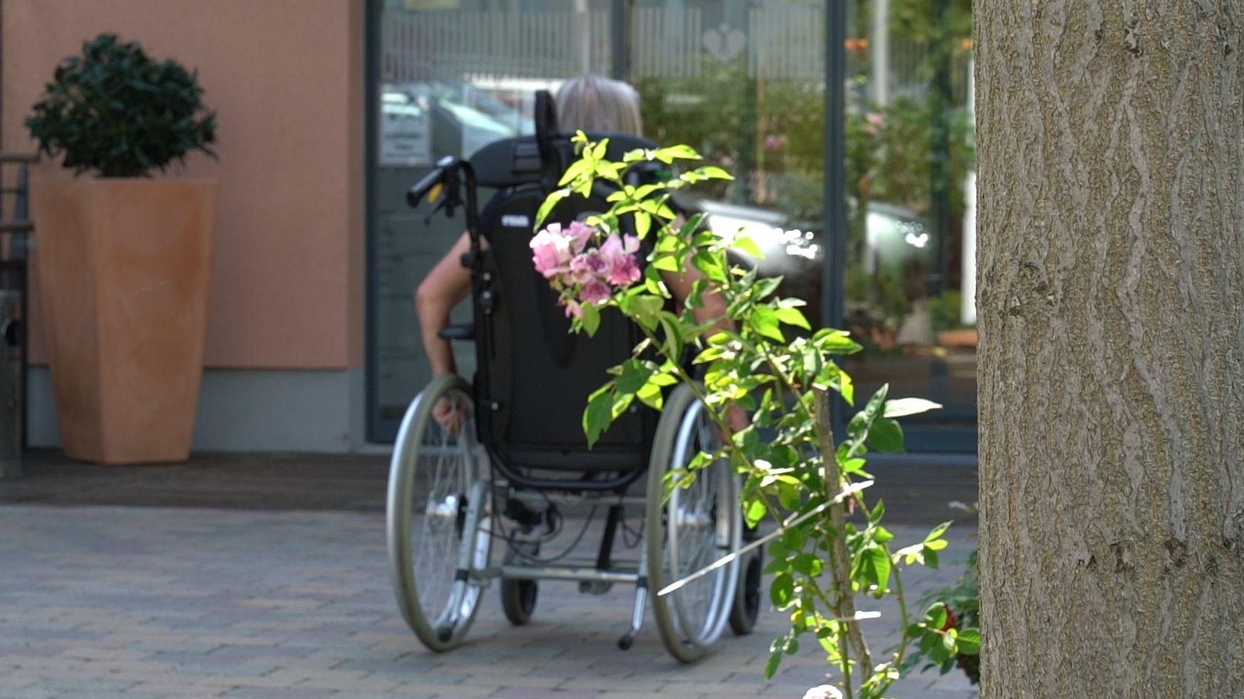 Rollstuhlfahrerin auf dem Gelände eines Seniorenheims