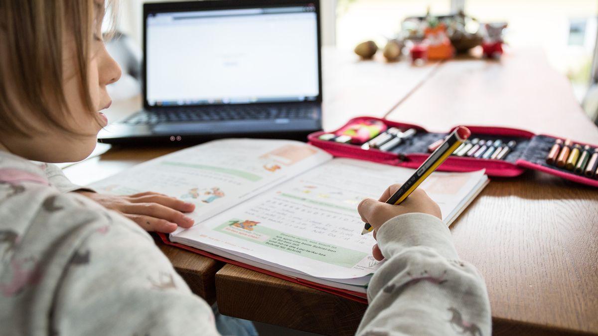 Symbolfoto: Ein junges Maedchen sitzt am Wohnzimmertisch an einem Laptop und macht Homeschooling