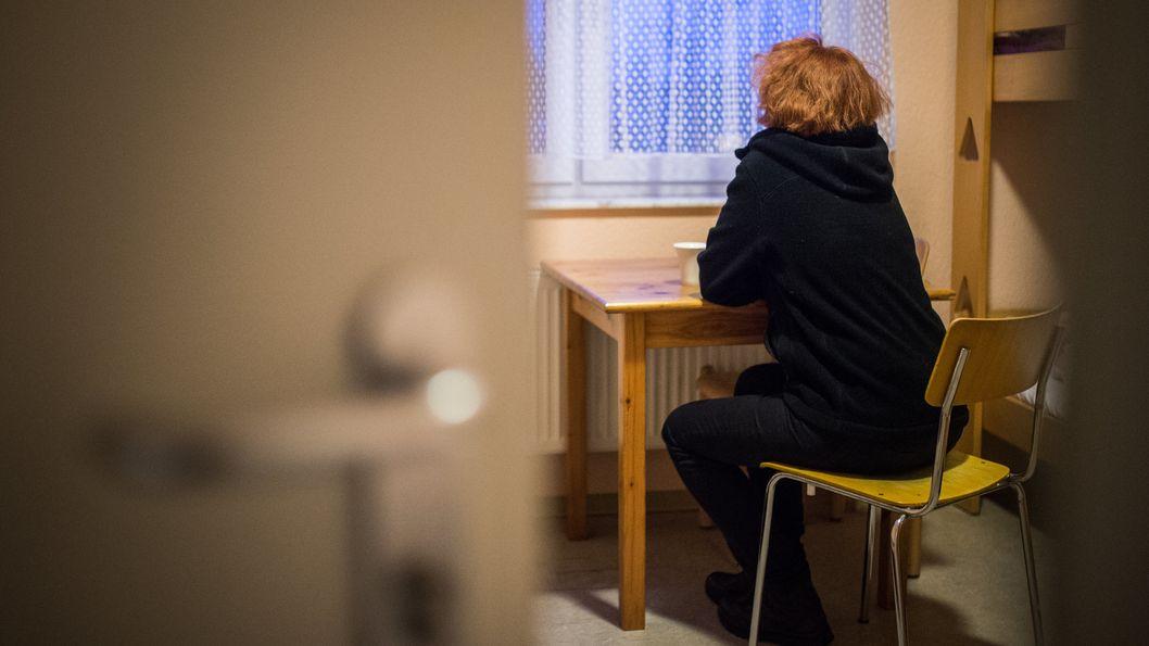 Eine Frau sitzt in einem Zimmer im Frauenhaus und schaut aus dem Fenster.