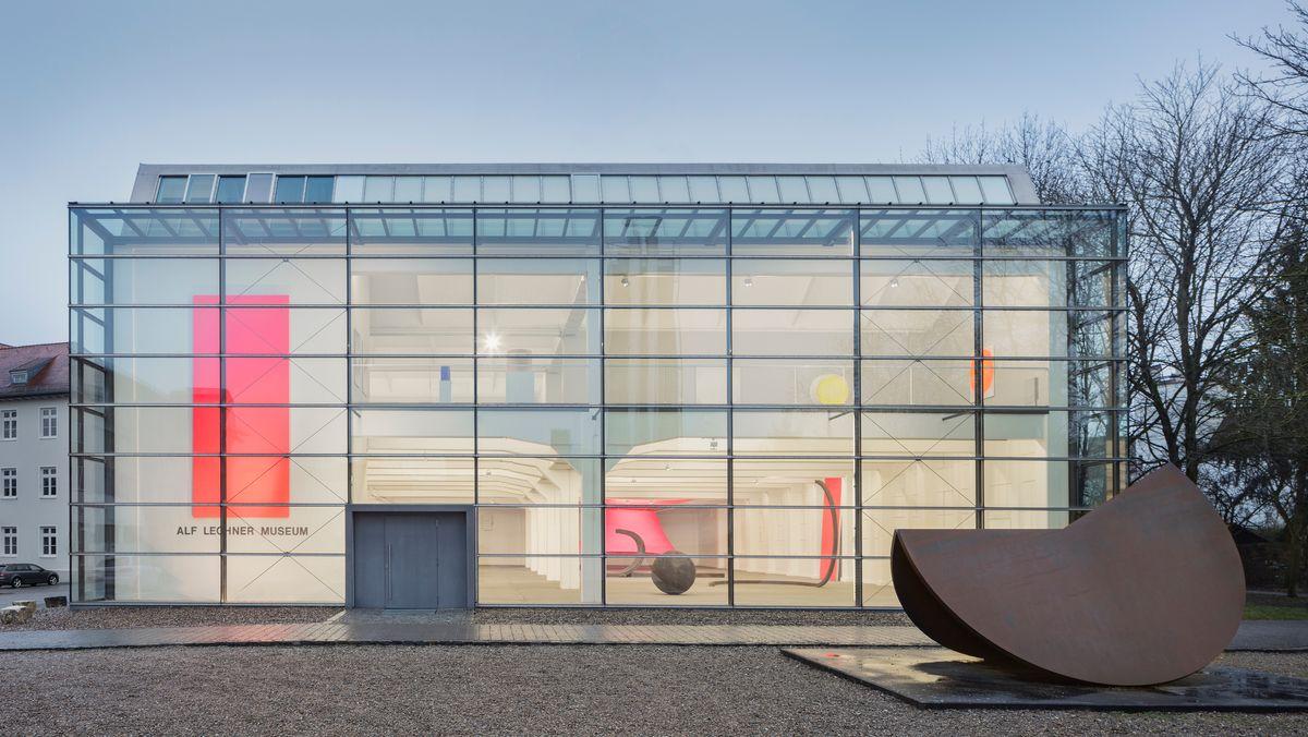 Außenansicht des gläsernen zweistöckigen Museums, in das man von außen schauen kann und die roten Gemälde und die Stahlskulpturen sehen kann.