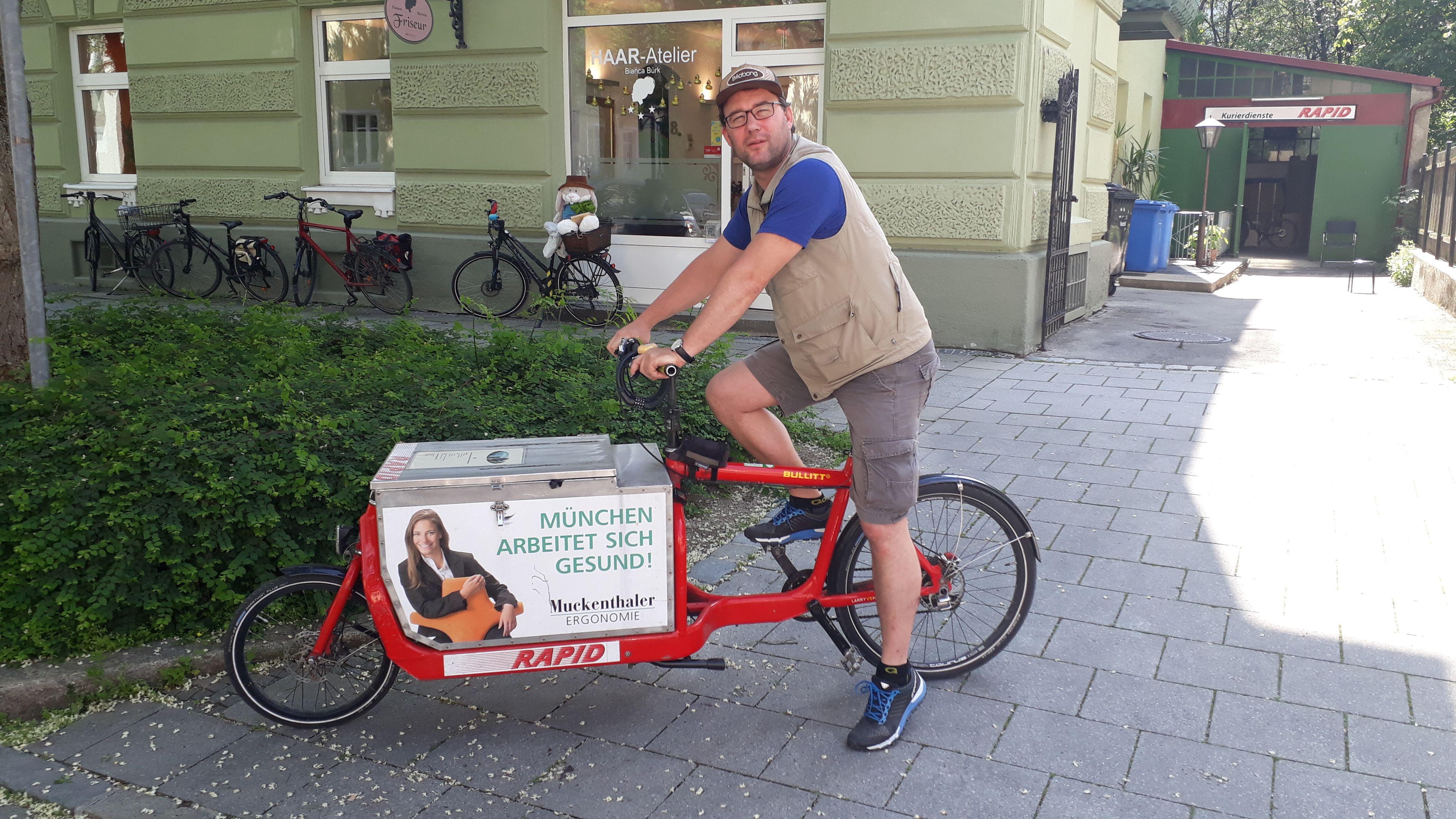"""Fahrradkurier Stefan Kerscher posiert mit seinem Fahrrad mit der Aufschrift """"München arbeitet sich gesund""""."""