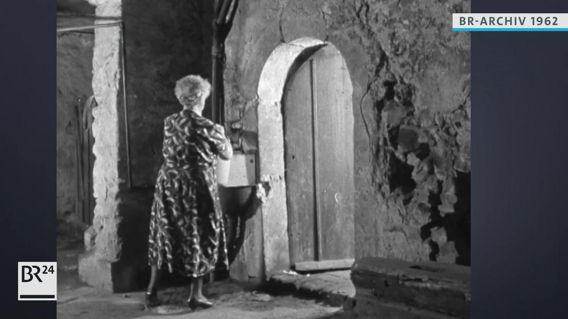 Frau beim Befüllen eines Wassereimers an einem zentralen Wasserhahn