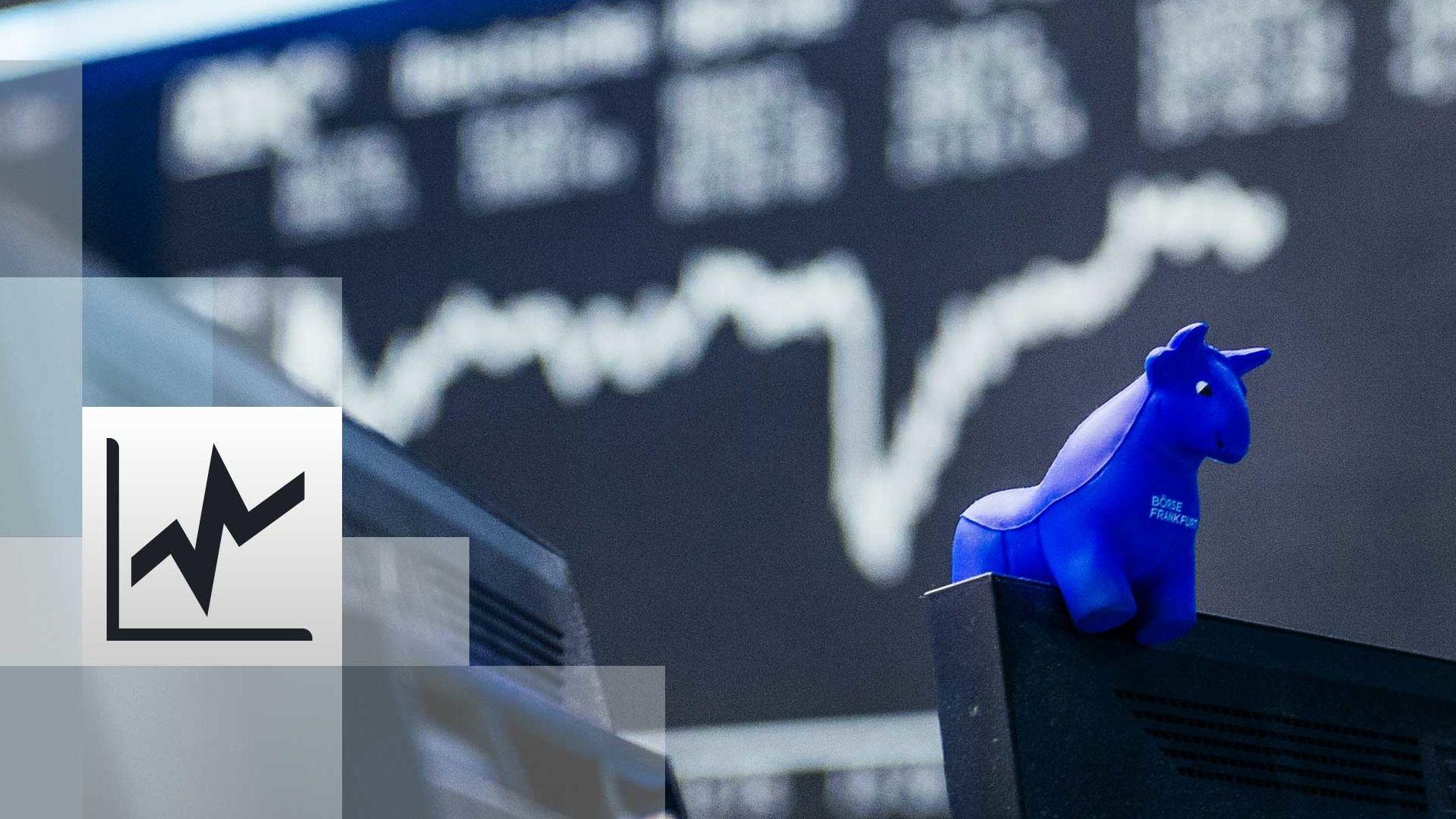 ein blauer Stieraus Gummi sitzt auf der oberen Kante eines Bildschirmes, im Hintergrund die Kurstafel der Börse