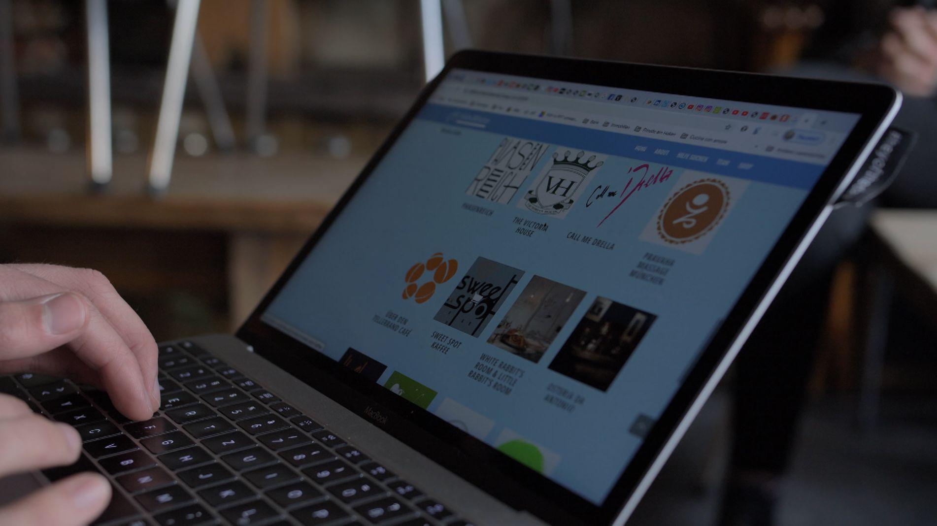 Aufgeklappter Laptop mit Logos der Läden der Gutschein-Plattform helfen-münchen.de