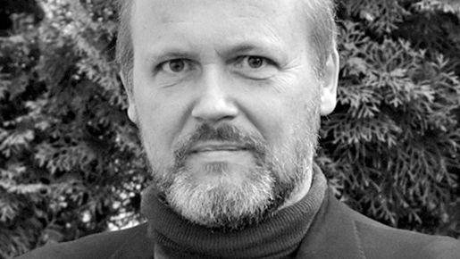 Wolfgang Ullrich blickt, vor einem Busch stehend, ernst in die Kamera (Schwarzweiß-Fotografie)