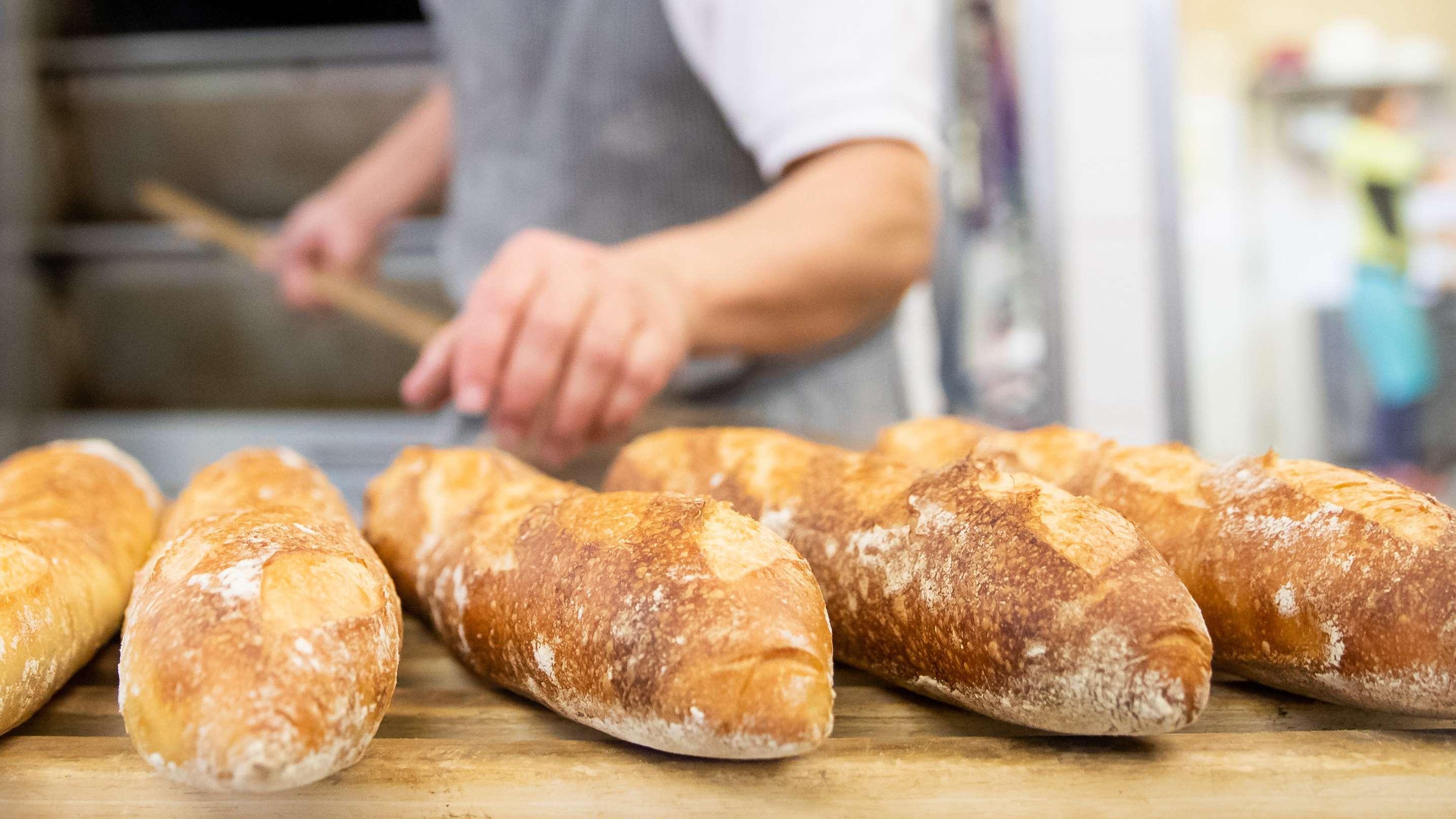 Bayern, Dachsbach: Ein Bäcker- und Konditormeister legt in der Backstube eines Betriebs Baguettes aus dem Ofen auf ein Brett.