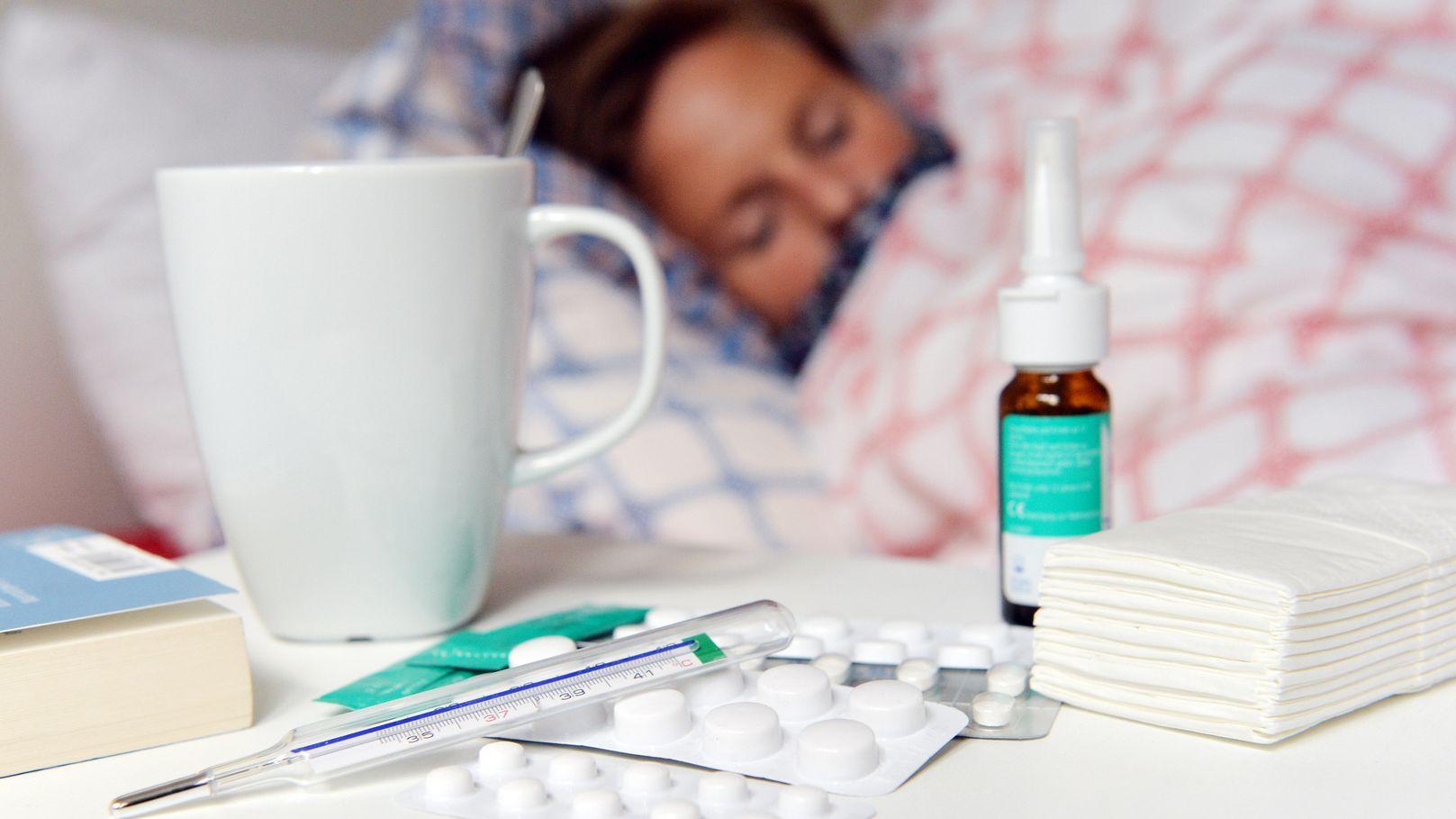 Frau im Bett, davor Medikamente und ein Fieberthermometer auf einem Nachttisch.