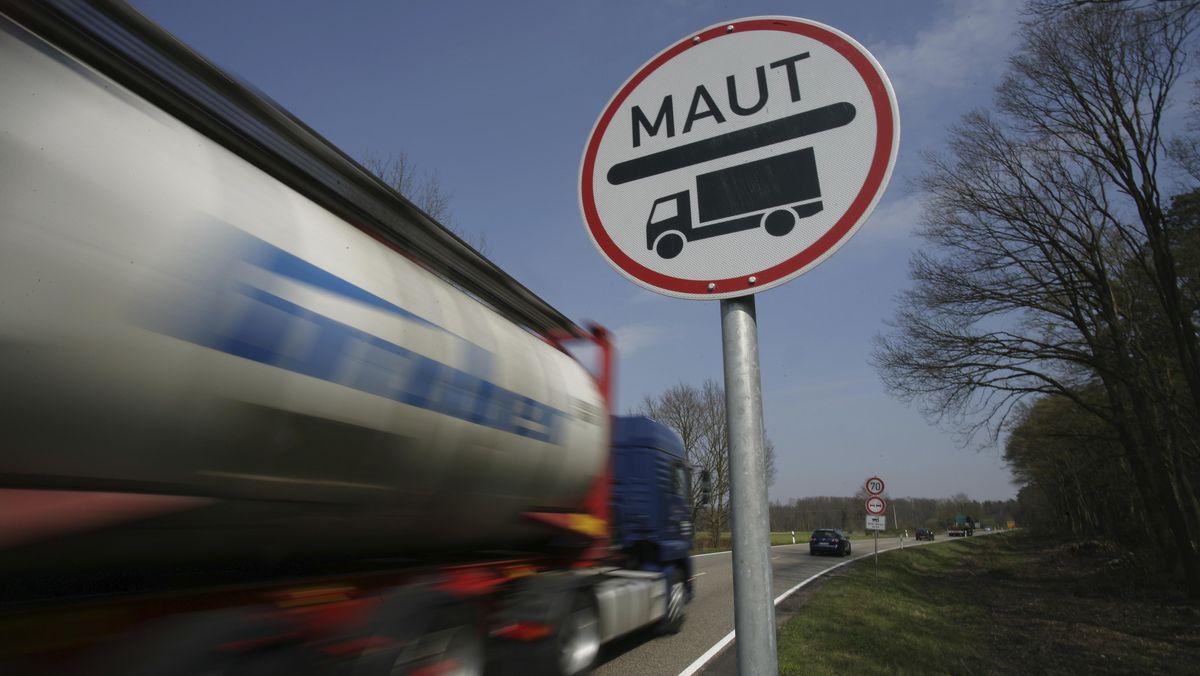 Ein Lastwagen passiert ein Hinweisschild auf die LKW-Maut