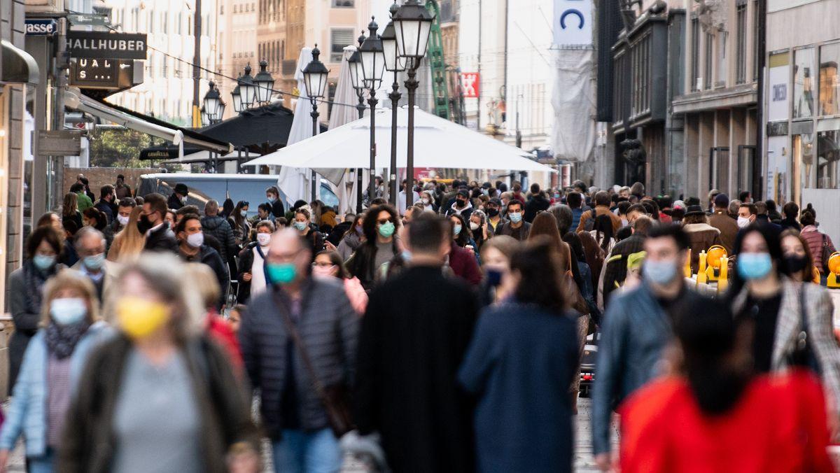 Zahlreiche Menschen gehen mit Mund- und Nasenbedeckung durch eine Einkaufsstraße in der Innenstadt von München.